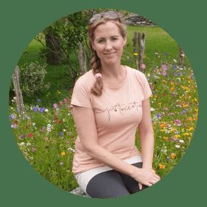 Aletta zittend voor een bloemenveld in Oostenrijk. Op het t-shirt dat zij draagt staat 'just breathe'